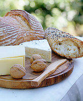 Detail of a wooden cheeseboard with cheese, bread and walnuts