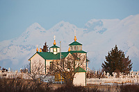 Mount Iliamna of the Aleutian mountain range, towers above a Russian Orthodox church, built in 1901, in the coastal town of Ninilchik on the Kenai Peninsula, southcentral, Alaska.