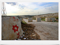 Concrete blocks block the exit of the Palestinian road   to Road No. 443. Road 443 is one of the main throughways of the West Bank. Its overall length is 25.5 KM, 14 out of which run through the heart of the West Bank. .With the break of the second Intifada at the end of 2000, Israel had severely restricted Palestinian movement on road 443, which was their main road from the Beit Sira, Saffa, Beit Liqiya, Kharbatha al-Misbah, Beit Ur al-Tahata, Beit Ur al-Foqqa and al-Tira villages to Ramallah. These restrictions were harshened in 2002, when Palestinian movement was completely prohibited. In recent years all entries and exits from the road to the area's villages were blocked with gates and concrete slabs. Photo by Quique Kierszenbaum