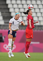 KASHIMA, JAPAN - AUGUST 2: Christine Sinclair #12 of Canada heads the ball in front of Julie Ertz #8 of the United States during a game between Canada and USWNT at Kashima Soccer Stadium on August 2, 2021 in Kashima, Japan.