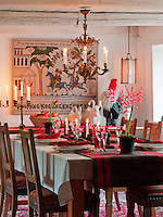 A dining table is decorated for Christmas, with warm, festive candlelight and ornaments