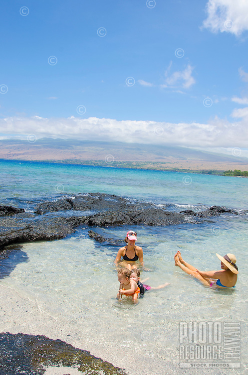 Two local moms smile while their children play in a tide pool at a beach in Puako, Big Island.