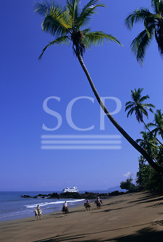 Osa Peninsula, Costa Rica. Group of tourists riding horses on the beach at Drake Bay with cruise ship behind.