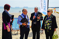 BNPS.co.uk (01202 558833)<br /> Pic: Graham Hunt/BNPS<br /> <br /> Town Mayor Cllr Colin Huckle talks to fellow councillors at the end of the meeting.<br /> <br /> Town hall officials swapped their stuffy chambers for the sand and sea today as they took part in what is thought to be the UK's first ever council meeting on a beach.<br /> <br /> Weymouth Town Council in Dorset held the event on the beach in protest at the Government banning virtual meetings.<br /> <br /> Since May 6, votes cast at virtual council meetings have not been legally binding following a controversial ruling upheld by a High Court judge.<br /> <br /> But because social distancing is difficult to practice in many town halls, officials in Weymouth used a loophole in the rules to meet on a beach.