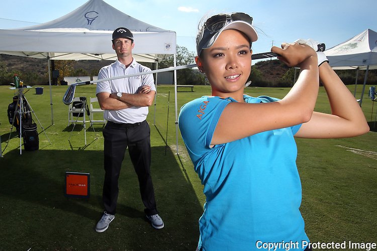 Carolyn Zhao, 15, takes a golf lesson from instructor Chris Mayson at Maderas Golf Club in Poway Friday. photo by Bill Wechter