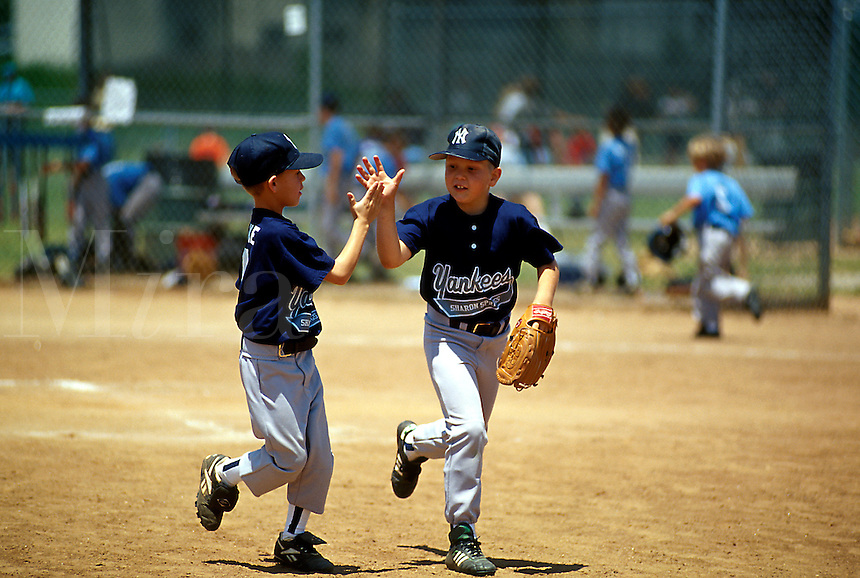 Young Little League baseball players run off the field as they exchange a high-five.