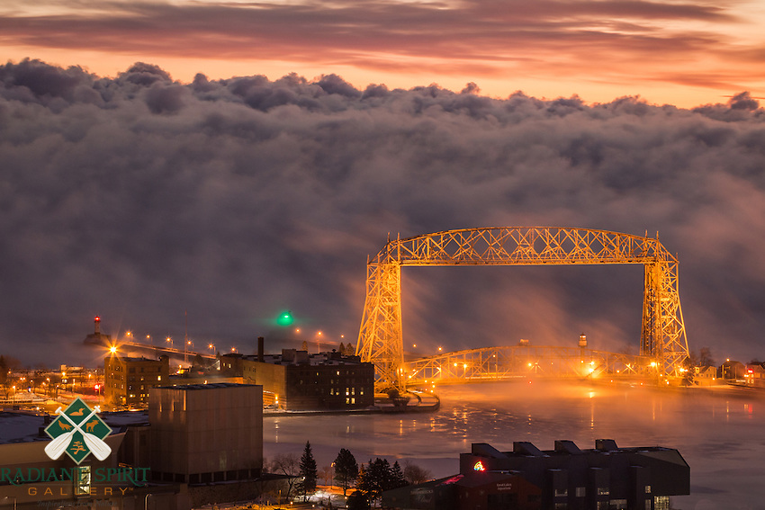 """""""Gateway to Winter""""<br /> The sea smoke was incredibly dense this morning at 12 below zero (F). The sea smoke is caused by evaporative cooling -- the cold air temperature and warmer open water of Lake Superior create this beautiful type of winter fog. Duluth winters are strikingly beautiful! This long exposure photograph gives the sea smoke a ghostly appearance as it glides past the Aerial Lift Bridge from the Duluth Harbor."""