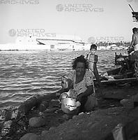 Alte Frau mit Topf und Junge an der Mündung des Rio Manzanares in Cumaná, Venezuela 1966. Old boy with pot and boy at the water mouth of the Rio Manzanares in Cumaná, Venezuela 1966.
