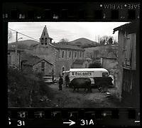 Village d'Arguenos (Haute-Garonne). 10 janvier 1978. Vue d'ensemble au coeur du village ; au 1er plan un homme de profil regarde le photographe, il est suivi par un atelage tiré par deux boeufs ; au 2nd plan camionette d'un marchand ambulant (Baignes), une dame est en train d'acheter quelque chose (vue de profil) ; en arrière-plan église.