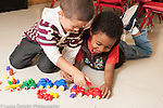 Education preschool first days of school 3-4 year olds two boys playing with toy vehicles and small plastic colored bears