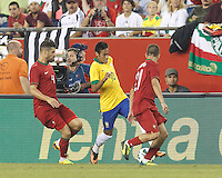 Brazil forward Neymar (10) dribbles down the wing as defenders close, Portugal midfielder Miguel Veloso (4) and Portugal defender Joao Pereira (21). In an international friendly, Brazil (yellow/blue) defeated Portugal (red), 3-1, at Gillette Stadium on September 10, 2013.