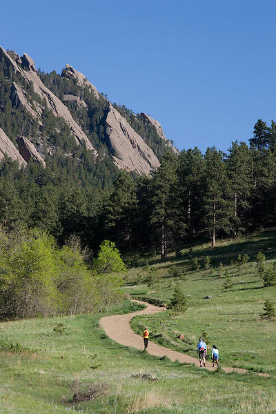 Caucasian male and female hikers and the Flatirons rock formation, Chautauqua Park, Foothills, Boulder, Colorado, USA .  John leads hiking and photo tours throughout Colorado. .  John leads private photo tours in Boulder and throughout Colorado. Year-round.