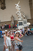 Young women photograph themselves in front of Giambologna's sculpture The Rape of the Sabine Women, Piazza della Signoria, Florence, Italy