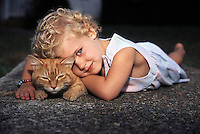 Little girl resting head on her cat