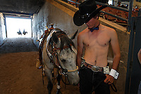 Dressed or undressed as a Chippendale dancer, Scott Lawrence and his mustang competed in the costume contest of the Western States Wild Horse and Burro Expo.  Eighty six horses were entered in various competitions in Reno, Nevada. His girlfriend DeAnn Rife waits with him.