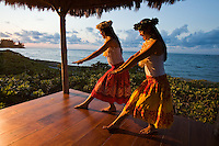 Young women practicing hula in a beachfront gazebo at sunset