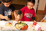 Preschool Headstart 3-5 year olds meal lunch time two boys serving themselves spagetti and tomato sauce and broccoli