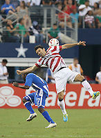 Michael Parkhurst #15 of the USMNT defends the ball from Diego Reyes #7 of Honduras on July 24, 2013 at Dallas Cowboys Stadium in Arlington, TX. USMNT won 3-1.