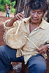 Angel Morinigo, an Mbya Guarani craftsman and musician from Andresito village near San Ignacio, Misiones, Argentina, playing a traditional drum (anguapu) he carved from the trunk of a palm tree.