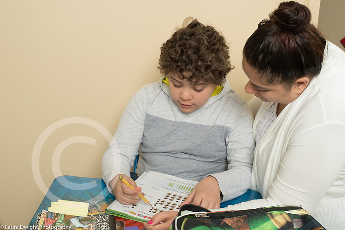 7 year old boy doing homework with help from mother