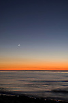 Windansea, La Jolla, California; a sliver of moon is visible over the Eastern Pacific Ocean at sunset