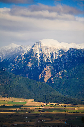A rocky cliff on the side of the Mission Mountains is lit by sunlight as snow still falls on the upper peaks