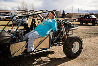 Les Baugh, 59, exits his favorite off-roading vehicle in the driveway of his house in Walden, Colorado.  Mr. Baugh, who lost both his arms at the shoulder in a freak electrical accident 40 years ago, has installed steering wheels on the floor of each of his vehicles so that he can drive. Since losing his arms, Baugh has managed life mostly without the help of prosthetic arms, which he finds to be more of an uncomfortable nuisance than a help. In 2013, Les underwent a state of the art surgery called Targeted Muscle Reinnervation, where the bundle of nerves at the stump of his shoulders were remapped to his pectoralis muscles. After he recovered from surgery, researchers at Johns Hopkins Applied Physics Lab fitted him with two robotic arms, called the MPL or Modular Prosthetic Limb, and he was able to manipulate objects with his hands, just by thinking about it. The MPL is a state of the art prototype, and not ready for take-home, so Baugh has been practicing mind control at home in rural Walden using a virtual reality game paired with less advanced prosthetic limbs. At a later stage the researchers at Johns Hopkins hope to get Les to try more advanced versions of the MPL  in the hope that his remapped nerves will have grown deeper into his pecs and he'll be able to manipulate the arms more effectively.