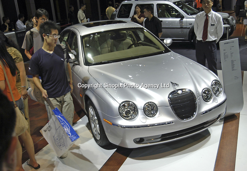 Visitors look at a Jaguar S-type at the Auto China 2004 exhibition in Beijing, China..