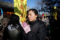CHINA. A woman praying during Chinese New Year in Baiyun Temple in Beijing.  Chinese New Year, or Spring Festival, is the most important festival and holiday in the Chinese calendar In mainland China, many people use this holiday to visit family and friends and also visit local temples to offer prayers to their ancestors. The roots of Chinese New Year lie in combined influences from Buddhism, Taoism, Confucianism, and folk religions.  2008