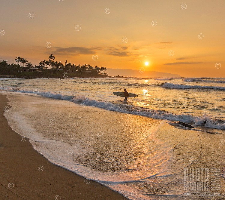 A surfer brings his board out of the water near Chun's Reef as the sun sets over the North Shore of O'ahu; Ka'ena Point is in the distance.