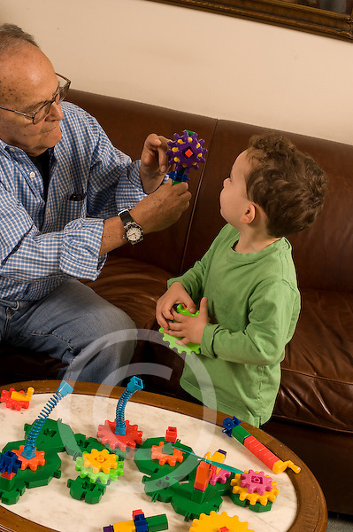 Grandfather in his early 80s playing with plastic interlocking gear toy and his 3 year old grandson vertical Caucasian