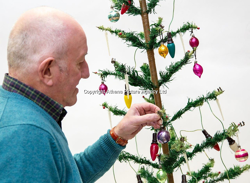 "PLEASE BYLINE Hansons Auctioneers Ltd/Athena Pictures<br /> Pictured: Steve Rose decorates his Christmas tree<br /> Re: One of the first mass-produced Christmas trees will be sold at auction after owned by the same family for 80 years.<br /> The parents of Steve Rose, 74, used to decorate the vintage 1937 tree which they bought from Woolworths, every year in their home in Markham, Caerphilly and kept on with the tradition after they died.<br /> But Mr Rose feels it is time to say goodbye and give someone else the chance to create a simple, vintage Christmas.<br /> The tree is offered for sale alongside Mr Rose's lights and baubles and has an estimate of £200-300, but a similar item sold last year without any decorations for £420.<br /> Mr Rose, a retired Biology teacher, the only son of a miner, is parting with his heirlooms because he has no children to leave them to.<br /> ""It was our main family tree for years and I remember my mum putting it up every Christmas,"" he said.<br /> ""Christmas was not an extravagant affair... in the late 1940s you'd get a Christmas sock and inside it was a tangerine, nuts, some loose change and small presents."
