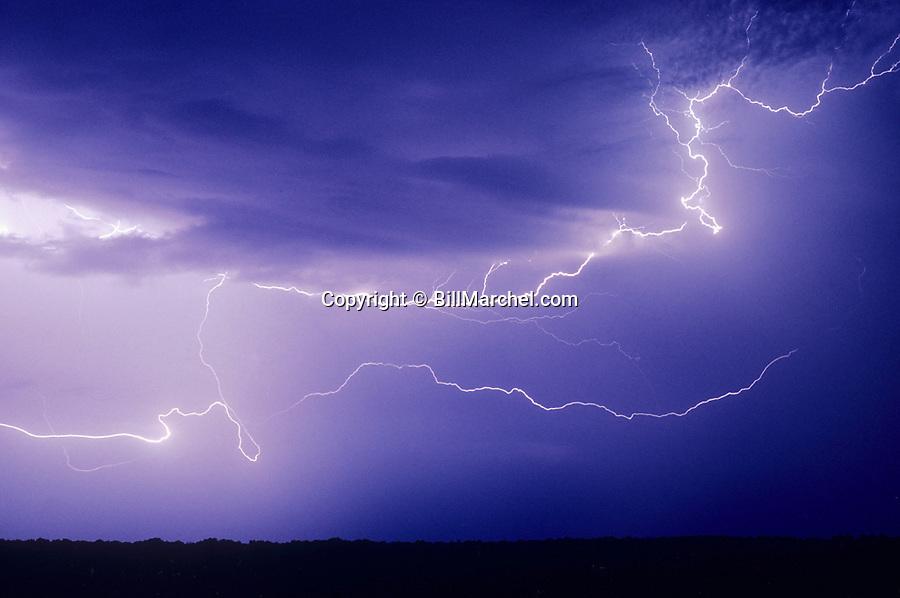 00715-001.01 Lightning bolt travels cloud-to-cloud against grey, nighttime sky.