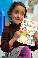Chefchaouen, Morocco.  Little Girl Displaying her School Book Used to Learn the Arabic Alphabet.