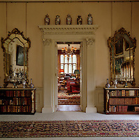 The grand entrance to the library is flanked by a pair of gilt-framed mirrors above matching Empire bookshelves