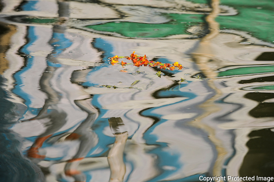 Floating fowers in the reflection in river Ganges in Varanasi