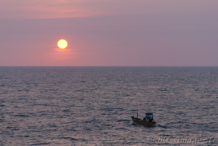 Fishing boat heads out to sea at sundown -Beruwala, Sri Lanka