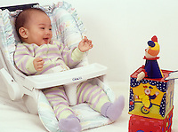 Seven month old baby girl sitting in infant seat excited by Jack-in-the-box toy