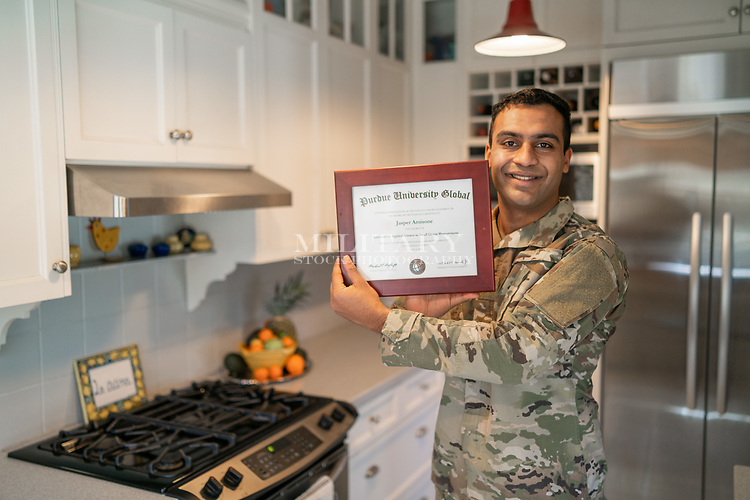 Happy young off duty US Army soldier at home in his kitchen, for sale as stock photography, diploma