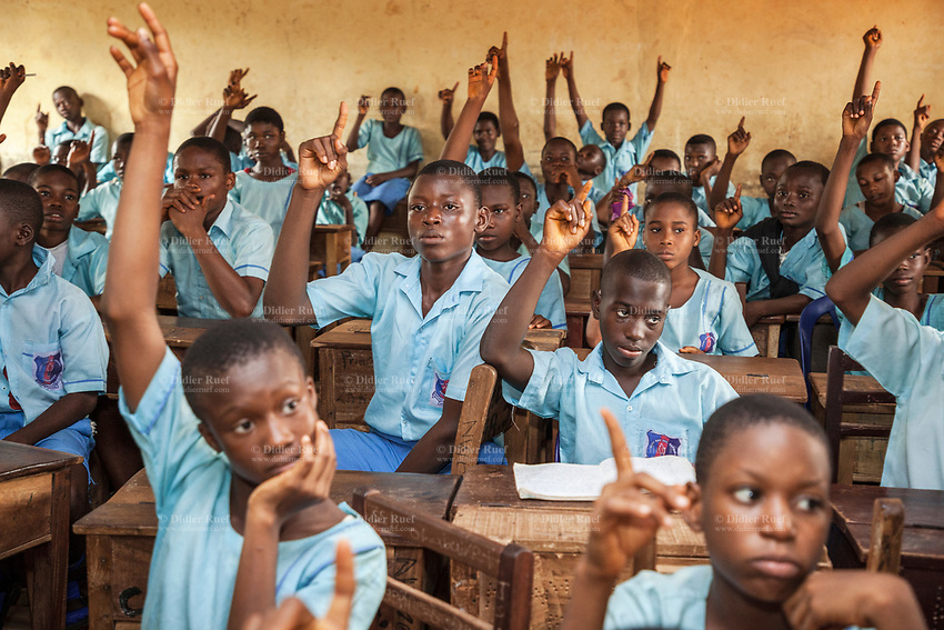 Nigeria. Enugu State. Enugu. Army Day Secondary School ( Awkunanaw in Igbo language). Igbo students raise hands in the classroom. They signal that they know the answer. Wooden desks. The pupils, boys and girls, wear blue uniforms and are 12-13 years old. They belong to the class JS2, Junior Secondary School. The Army Day Secondary School was inaugurated in October 1998. Enugu is the capital of Enugu State, located in southeastern Nigeria. 11.07.19 © 2019 Didier Ruef