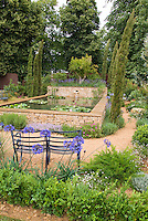 Dry plants next to raised water garden: Blue agapanthus next to garden bench in dry sandy Mediterranean garden with herbs Thymes Thymus, rosemary rosmarinus, boxwood buxus, Geranium, Lavandula lavender, raised stone water garden and fountain waterfall with waterlily plants Nymphaea water lilies, lovely backyard