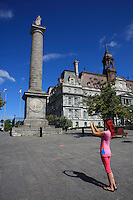 Montreal quebec CANADA - july 02, 2012 - MODEL RELEASED ILLUSTRATION - adult female walking around in Old-Montreal taking picture in front of the City Hall with her smart phone.