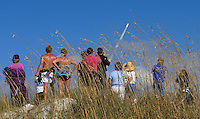 Beachgoers watch from a sand dune as Space Shuttle Columbia blasts off on the STS 107 Mission carrying a crew of seven (Rick Husband, Willie McCool, Michael Anderson, Kalpana Chawla, David Brown, Laurel Clark and the first Israeli astronaut,  Ilan Ramon) into orbit, Cocoa Beach, FL, January 16, 2003. The mission ended tragically as the Space Shuttle disintegrated during its terun to Earth in February 2003.  (Photo by Brian Cleary/www.bcpix.com)