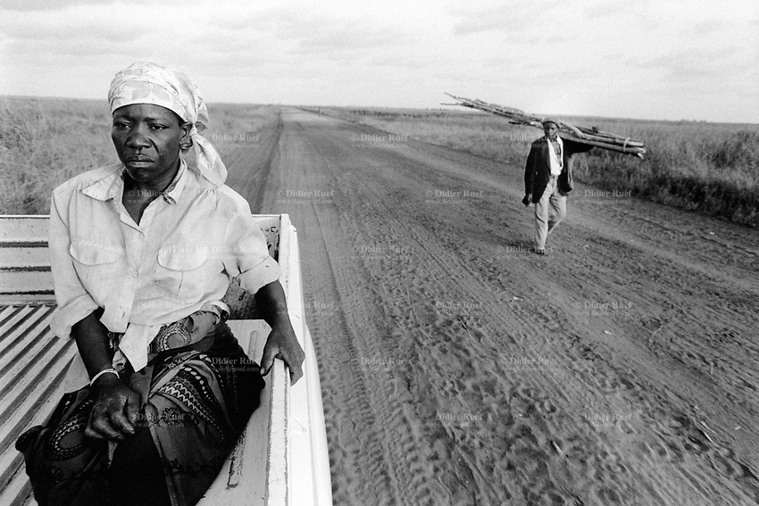 Mozambique. Province of Maputo. Manhiça is a small town (80 km north of the capital Maputo). A woman is seated on the back of a pick-up truck which belongs to the non governmental organisation (ngo) Médecins Sans Frontières (MSF) of Switzerland which has rehabilitated the local hospital. A man walks on the dirt road and carries wood sticks on his shoulder. © 1992 Didier Ruef