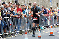 Pictured: A visibly upset Gareth Thomas continues his run after being embraced by his husband Stephen minutes after he started his marathon run. Sunday 15 September 2019<br /> Re: Ironman triathlon event in Tenby, Wales, UK.