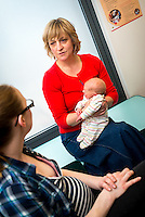 """Part of a series of photos in which a midwife listens to the difficulties a young woman has with breastfeeding her baby, finds that the baby has a tongue-tie, performs a tongue-tie division, helps the mother achieve a better latch and then gives the final bits of advice while doing her paper work.<br /> <br /> Image from the breastfeeding collection of the """"We Do It In Public"""" documentary photography picture library project: <br />  www.breastfeedinginpublic.co.uk<br /> <br /> Hampshire, England, UK<br /> 13/03/2013<br /> <br /> © Paul Carter / wdiip.co.uk"""