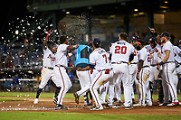 Mississippi Braves Wendell Rijo (11) is mobbed as he crosses home plate after hitting what was originally called a walk-off home run during a game against the Biloxi Shuckers on August 12, 2021 at Trustmark Park in Pearl, Mississippi.  The umpires would rule Rijo did not touch first base resulting in an out with the winning run still scoring from second base.  (Mike Janes/Four Seam Images)
