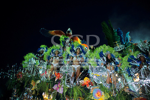 Rio de Janeiro, Brazil. Carnival; girls dancing on a float with rainforest, macaws, satellite dishes; Portela samba school.