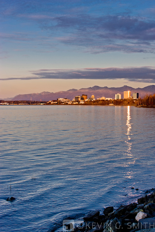 The Anchorage City Skyline reflected in the waters of Knik arm at sunset, high tide, taken from the Tony Knowles Coastal Trail, fall, Southcentral Alaska, USA.