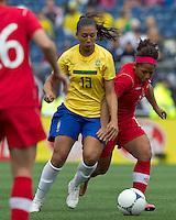 Brazilian midfielder Beatriz (13) dribbles as Canadian midfielder Desiree Scott (11) defends. In an international friendly, Canada defeated Brasil, 2-1, at Gillette Stadium on March 24, 2012.